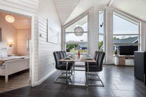 Blick auf den Esstisch vor der großen Fensterfront und ins angrenzende Schlafzimmer vom Ferienhaus in Schönberg