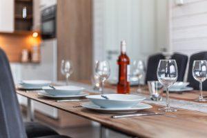 Edel gedeckter Tisch mit weißem Geschirr und Weingläsern aus dem umfangreichen Inventar laden zum Urlaub ein