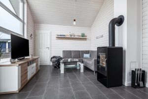 Gemütliches Ecksofa, großer Fernseher und moderner Kaminofen im Ferienhaus Küstenzauber