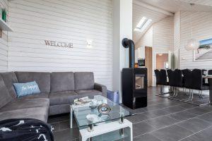 Wohnbereich mit Blick zum Esstisch und zur Küche, ein Kamin gehört zur exclusiven Ausstattung des Ferienhauses