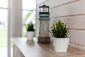Dekoration wie ein Leuchtturm und Gräser darf im Ferienhaus Küstenzauber für einen entspannten Urlaub nicht fehlen