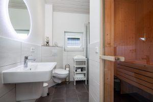 Zur Einrichtung gehört ein modernes Badezimmer mit Sauna im Ferienhaus an der Ostsee