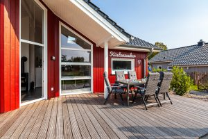 Zur Einrichtung gehören gemütliche Terrassenmöbel in grau auf der Holzterrasse vor dem schwedenroten Ferienhaus