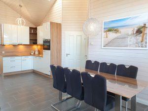 Esstisch mit 6 Stühlen und moderne weiße und holzfarbene Küche in L-Form