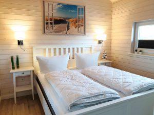 Weißes Doppelbett im gemütlichen Ferienhaus Küstenzauber